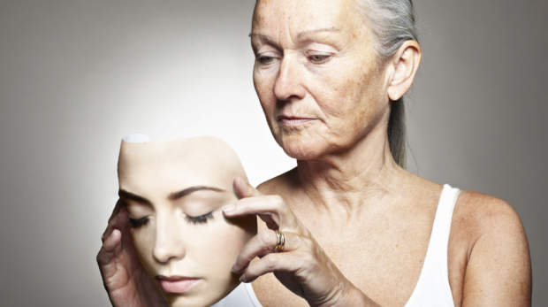 Older woman holding young mask